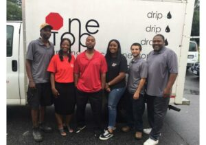 The One Stop Plumbing team members in red, black and gray shirts standing in front of the One Stop Plumbing truck.