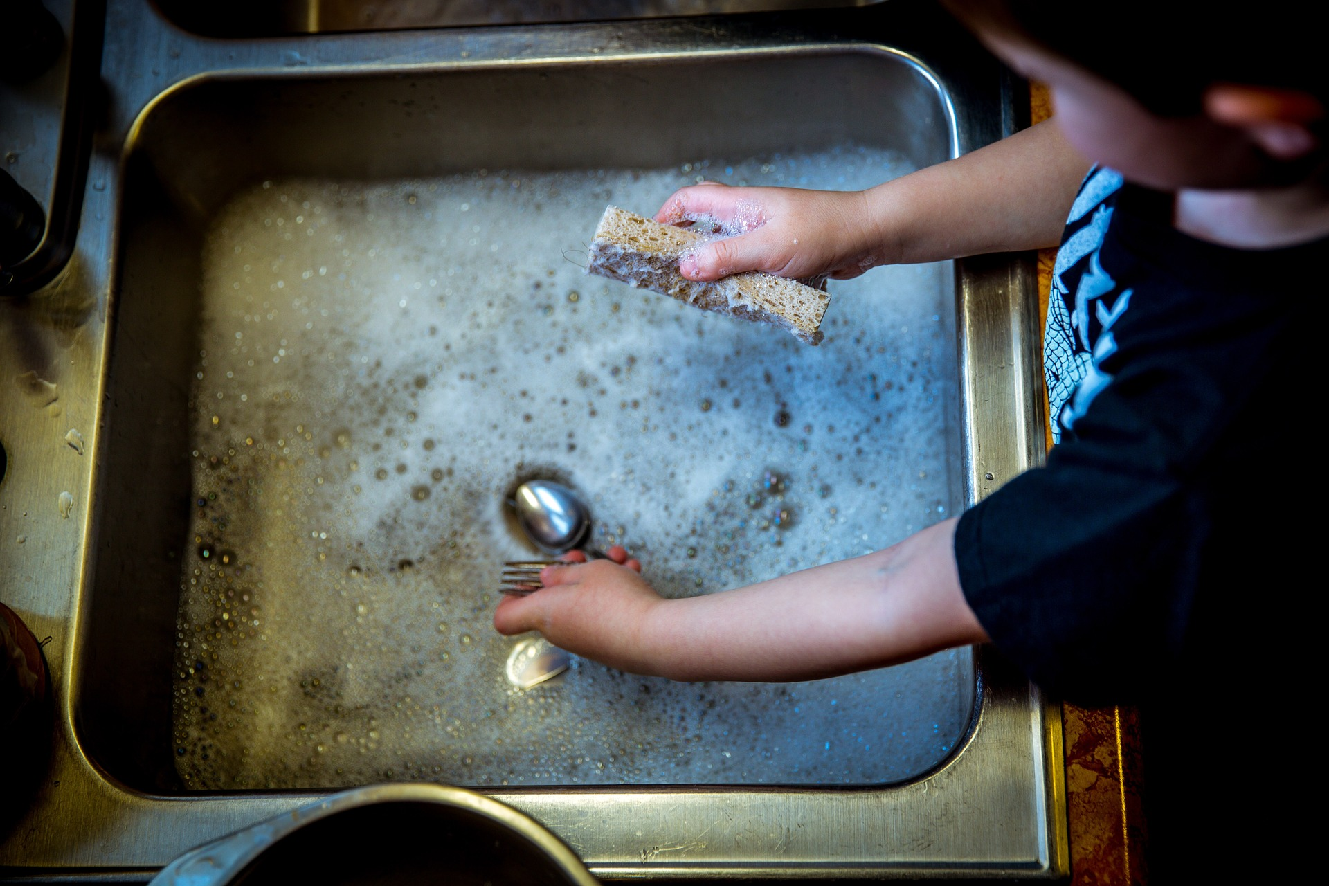 Child standing at the kitchen sink that is full of water and dishes on the One Stop Plumbing drain cleaning page