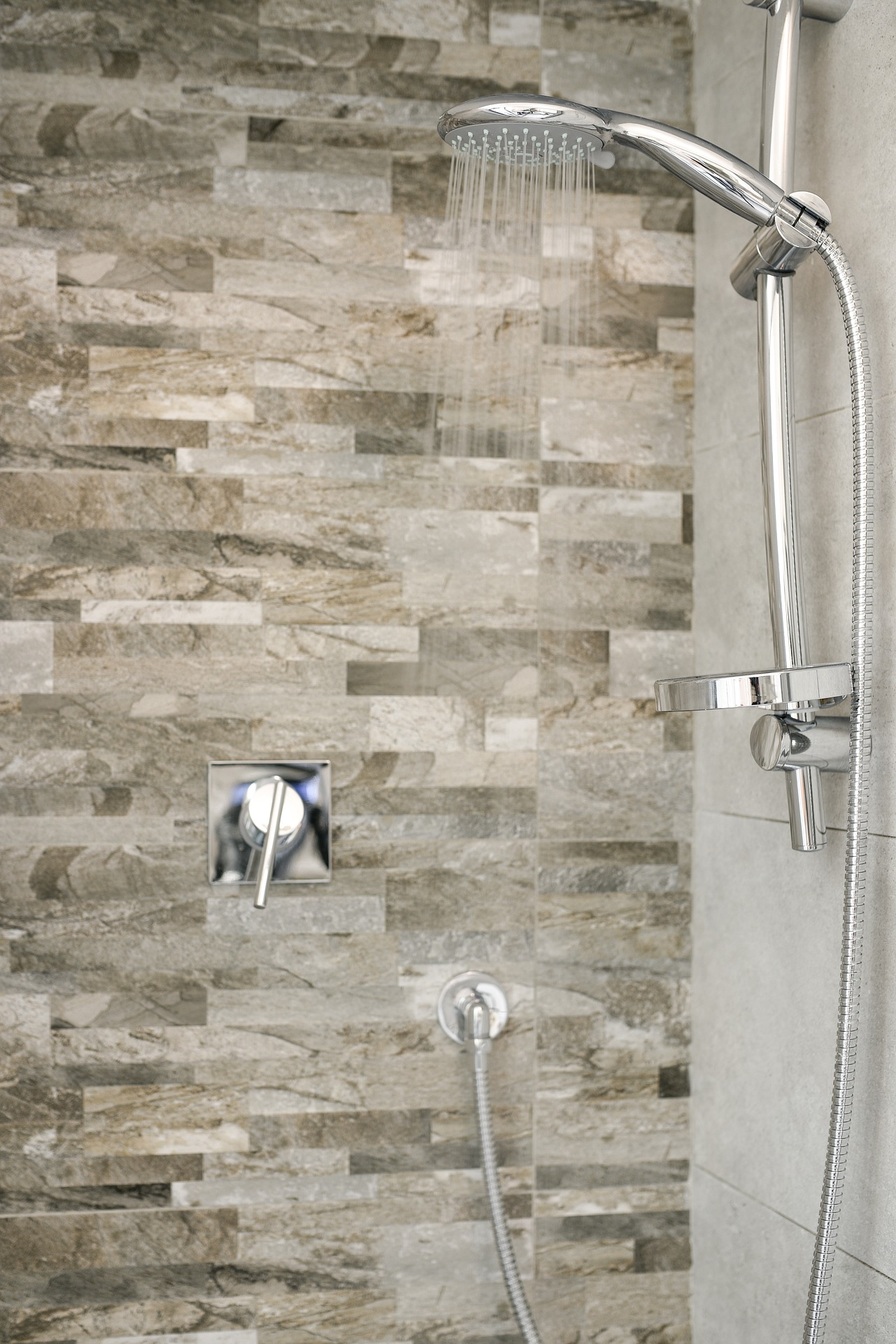 Shower with stainless steel fixtures and brown, black and white tiles on the One Stop Plumbing Do It Yourself DIY page