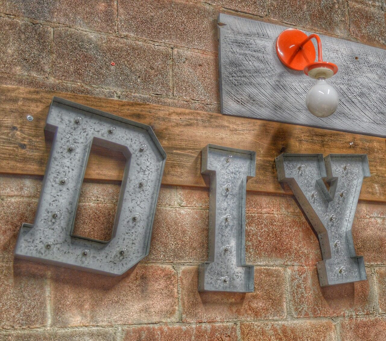 The letters DIY in metal hanging on a brick wall with a red light fixture on the One Stop Plumbing Do It Yourself DIY page