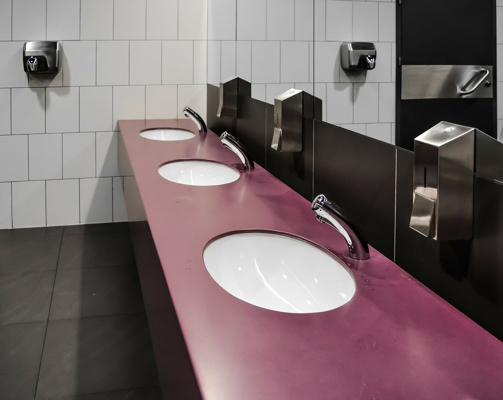 A black, red and white commercial bathroom with 3 sinks, mirror and hand dryer on the One Stop Plumbing commercial Plumbing page