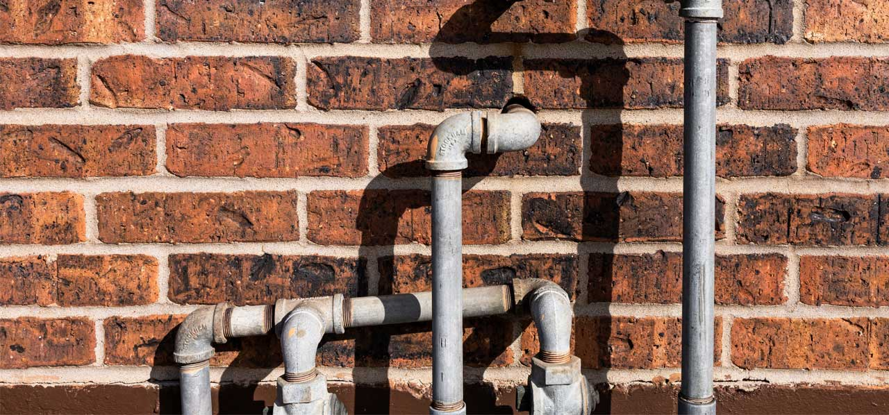 Brick wall with plumbing pipes entering the brick